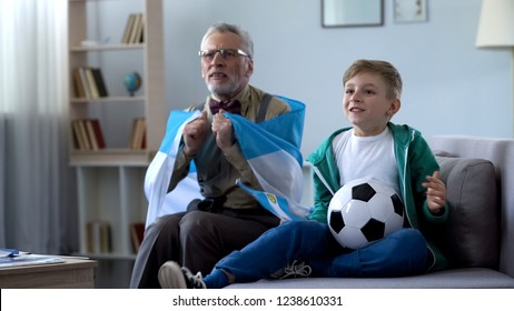 Granddad wrapped in Argentina flag watching soccer with boy, worrying about game