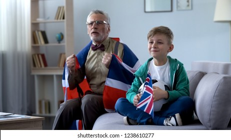 Granddad wrapped in British flag watching soccer with boy, worrying about game