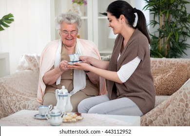 Granddaughter giving a cup of tea to her grandma