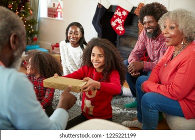 Granddaughter Giving Grandfather Gift As Multi Generation Family Celebrate Christmas At Home