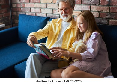 granddaughter and grandfatherlooking at photos together in a photo album, little girl listen to stories from life by grandpa