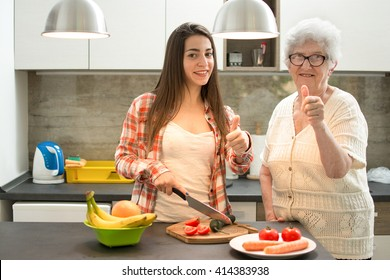 Granddaughter with grandmother cooking and showing thumbs up in the kitchen.