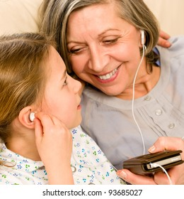 Granddaughter and grandmother listen to mp3 music headphones together smiling