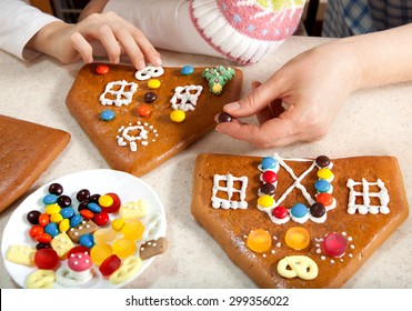 Granddaughter and Grandmother Making the Roof of Christmas Gingerbread House