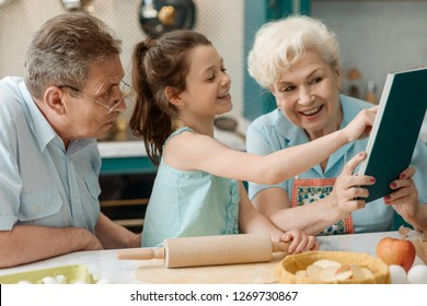 Granddaughter and grandparents cooking together. Child reading a recipe from a cookbook beside happy elderly couple.