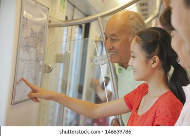 Granddaughter with grandparents standing in the subway and looking at the map