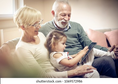 Granddaughter with grandparents using digital tablet.