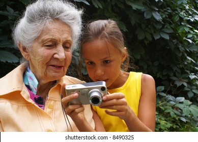 Granddaughter and her grandmother review digital camera pictures