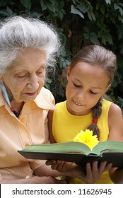 Granddaughter and her grandmother together reading a book