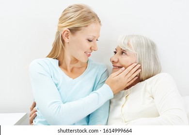 Granddaughter lovingly caresses the cheek of her old grandmother