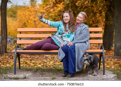 Granddaughter makes selfie with grandmother with a slight smile in the autumn park