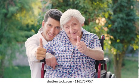 Granddaughter, nurse, caring for the elderly, boy(man) hugging grandmother, smiling, happy, walking in the park. Concept: boarding house, sanatorium, a house for the elderly, help for the elderly.