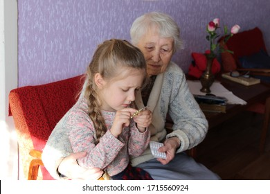 The granddaughter with pills and grandmother at home. The Covid-19, health, safety and pandemic concept. Selective focus
