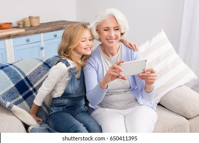Granddaughter taught grandmother how to make self-photos, selfies on mobile or smart phone. Pretty ladies taking photos while smiling for camera.