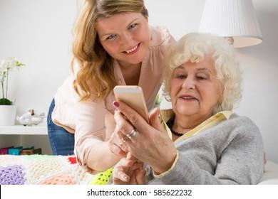 Granddaughter teaching grandma how to use smartphone