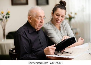 Granddaughter teaching her grandfather how to use digital tablet at home