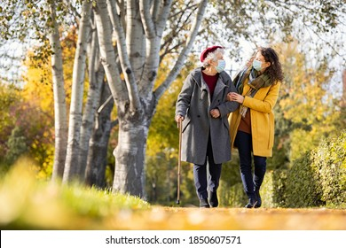 Granddaughter walking with senior woman in park wearing face mask for safety against covid-19. Old grandmother wearing surgical mask walking with lovely caregiver girl in sunny day after quarantine.