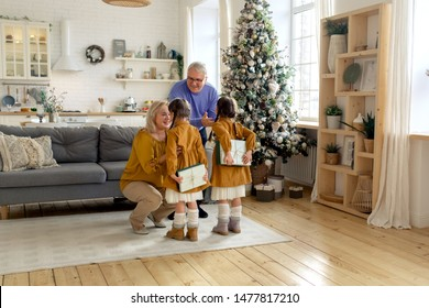 Granddaughters visit grandparents with gifts in the new year. Christmas. Family tradition