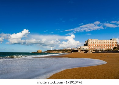 The Grande Plage form Biarritz under a partially cloudy blue sky. Famous Hotel du Palais in the background