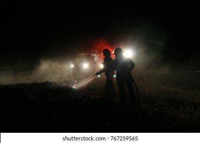 Grande Prairie, Canada - November 4, 2007: Firefighters are silhouetted by the lights of their firetruck as they put out a fire at night.
