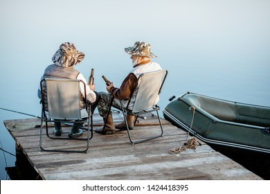 Grandfather with adult son enjoying beer, sitting together on the pier while fishing on the lake early in the morning