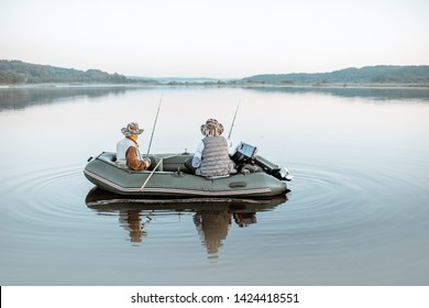 Grandfather with adult son fishing on the inflatable boat on the lake with calm water early in the morning. Wide landscape view