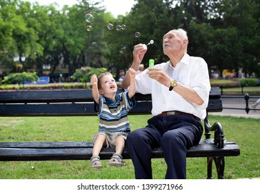 grandfather blowing soap bubbles to his grandchild on a bench
