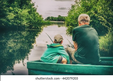 grandfather and boy fishing together. HDR. boy and an old man sitting in a boat with a fishing rod. view from the back