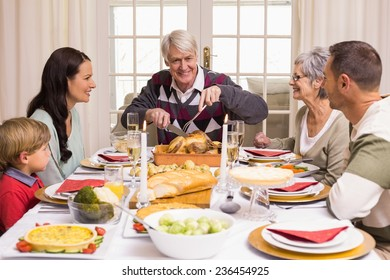 Grandfather carving chicken during christmas dinner at home in the living room