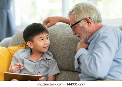Grandfather with child reading. Senior caucasian male with asian boy. using tablet together in living room at home.