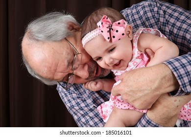 Grandfather cuddling his granddaughter against brown background