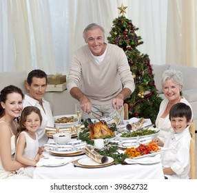Grandfather cutting turkey for Christmas dinner for his family