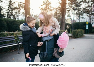 Grandfather enjoying with his grandchildren in city park.