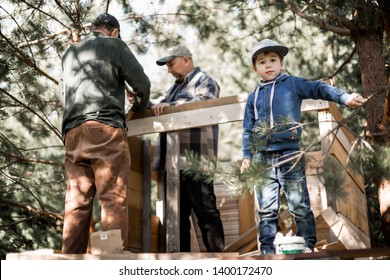 Grandfather, father and son are building a tree house together. Image with selective focus and toning