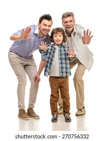Grandfather, father and son smiling and looking at camera, isolated a white background.