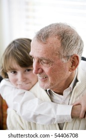 Grandfather getting hug from 9 year old grandson, focus on senior man