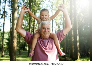 Grandfather giving granddaughter piggyback ride in park. Granddaughter sitting on shoulder of older man.