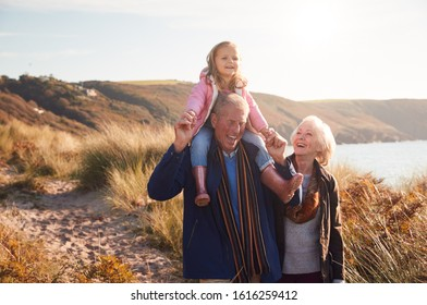 Grandfather Giving Granddaughter Ride On Shoulders As They Walk Through Sand Dunes With Grandmother