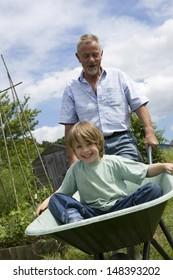 Grandfather giving grandson ride in wheelbarrow in community garden
