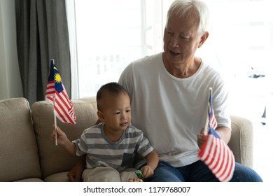 grandfather and gradson holding malaysia flag during national day