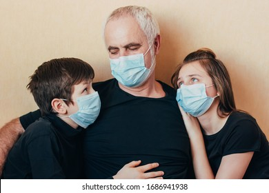 grandfather and grandchildren in face masks sit hugging sadly thinking about restrictions imposed due to coronavirus pandemic. Family support and care during quarantine and world epidemic