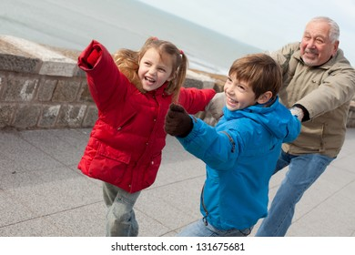 grandfather and grandchildren playing outdoors