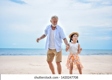 grandfather and grandchildren walking in tropical beach, elder with little girl on nature background