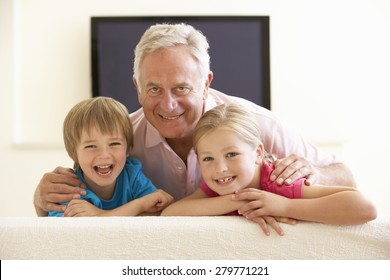Grandfather And Grandchildren Watching Widescreen TV At Home