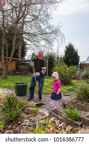 grandfather and granddaughter doing garden work cleaning the garden path