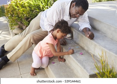 Grandfather And Granddaughter Drawing Picture On Steps