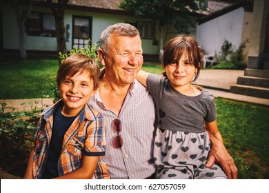 Grandfather with granddaughter and grandson kids outdoor
