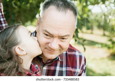 grandfather with granddaughter. Love you so much my grandpa. Grandpa kissing grandchild in the park. Multi generation family enjoying in the park.