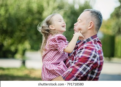 grandfather with granddaughter. Love you so much my grandpa. Grandpa kissing grandchild in thr park. Multi generation family enjoying in the park.