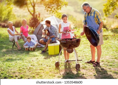 grandfather and granddaughter making barbeque for family